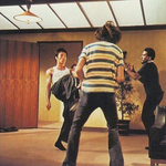 Bruce Lee kicking thug John Derbyshire (with striped T-shirt and back to camera) 