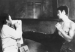 Bruce Lee kicking Robert Chan with a protecting pad in THE WAY OF THE DRAGON. This scene wasn't in the final movie like this, with Bruce Lee having his upper body naked. - Best guess: some kind of a rehearsal before the scene was shot