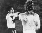 The showdown from THE WAY OF THE DRAGON: Bruce Lee displays the Wing Chun influence to his own Jeet Kune Do style against Karate opponent Chuck Norris.